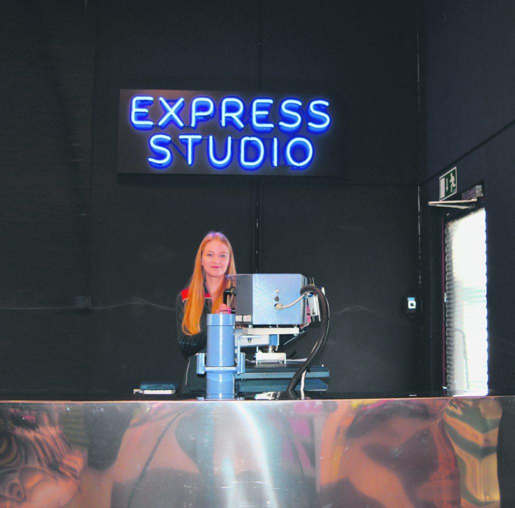 Express merkkaamossa Anni Hänninen painamassa asiakkaan logoja työtakkiin, asiakkaan odottaessa kahvikupin äärellä.