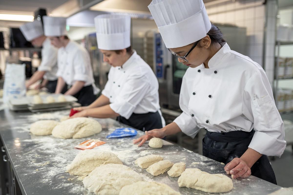 Kokkiopiskelijat leipomassa
