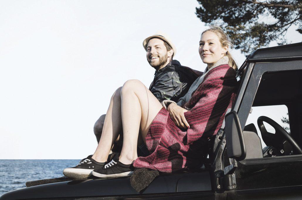 Kvinna och man vid havet sitter pmotorhuv pbil